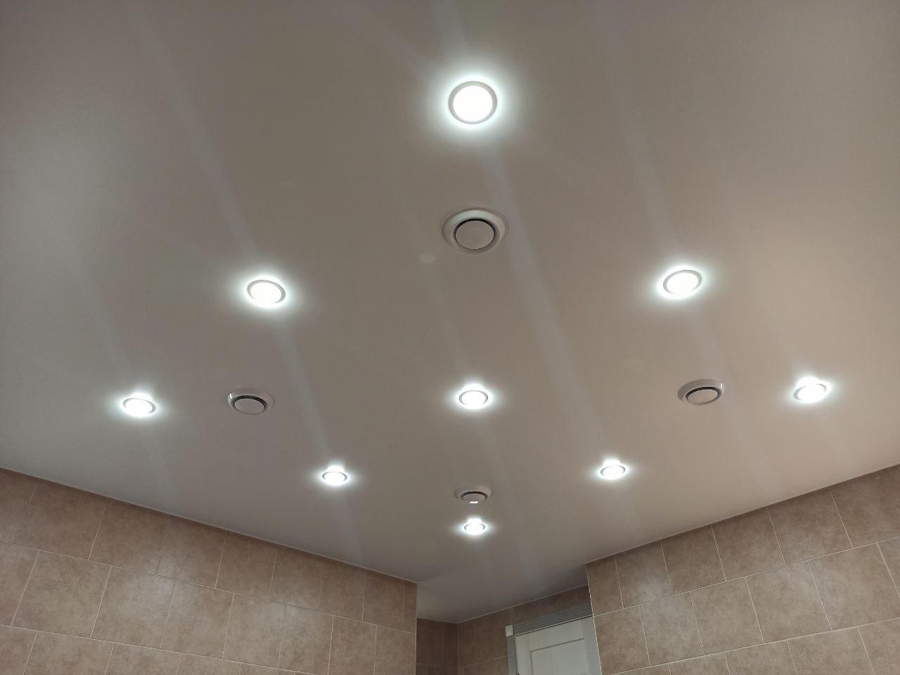 Матовый натяжной потолок в ванной комнате со светильниками.