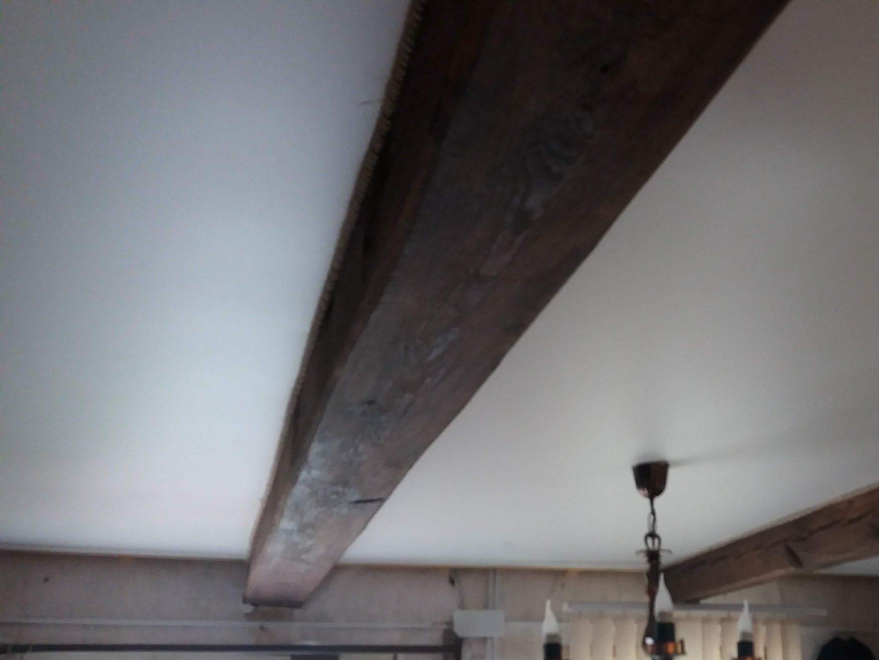 Матовый натяжной потолок между бревен на даче.