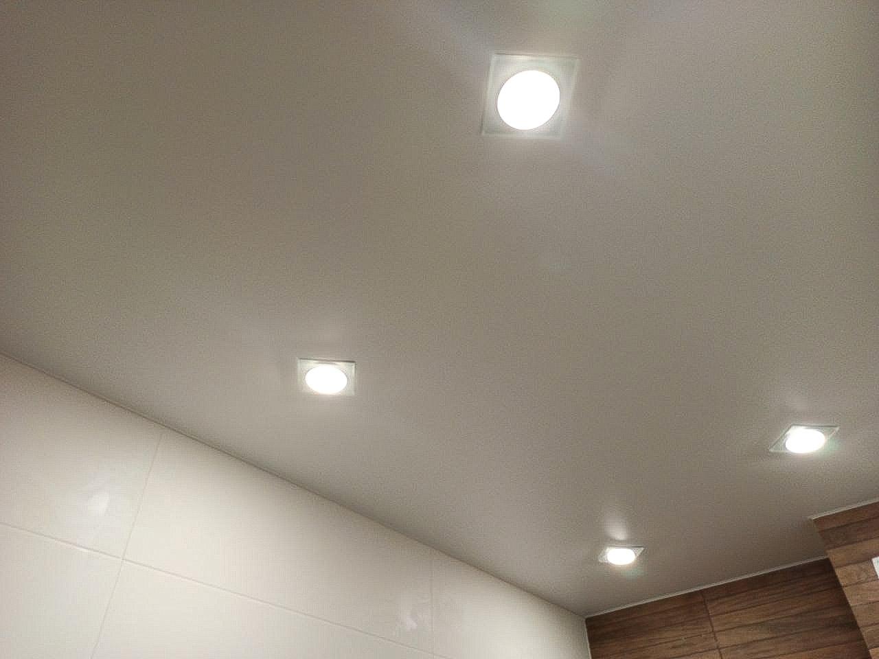 Сатиновый натяжной потолок в ванной с квадратными светильниками.